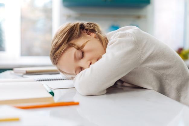 Симпатичная белокурая маленькая школьница спит над книгами, сидя за столом и делая домашнее задание