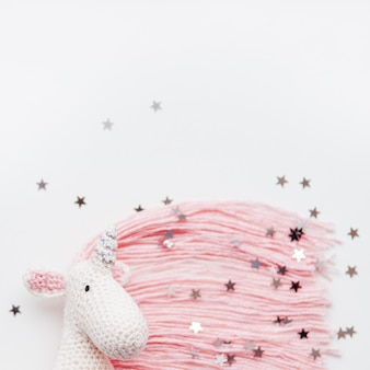 Cute fairy unicorn with a pink mane and a tail made of threads