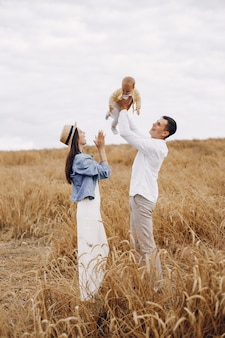 Cute family playing in a autumn field