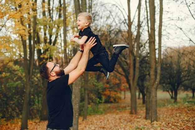 Милая семья играет в осеннем парке
