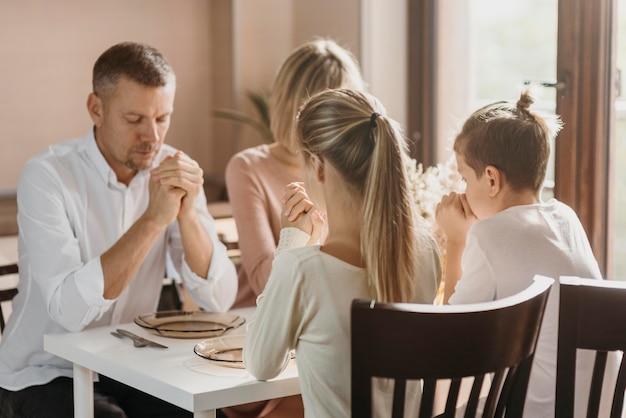 Famiglia carina che prega insieme prima di mangiare