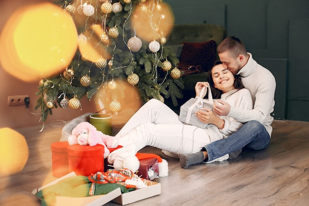 Cute family sitting at home near christmas tree