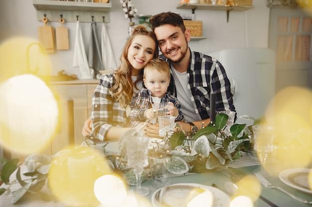 かわいい家族は台所に座っています。