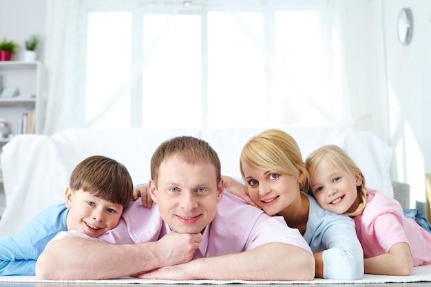 Симпатичные семьи улыбаясь вместе на дому