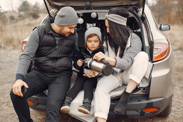 Cute family taking a hot drink in a winter field