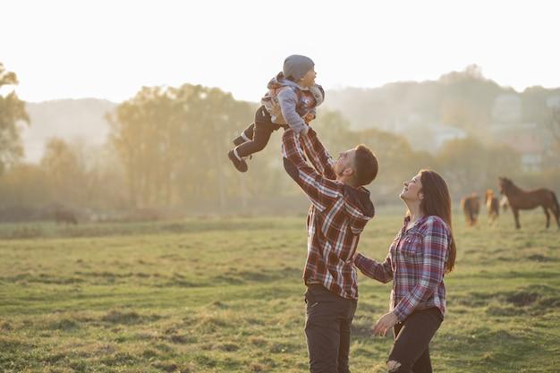 Милая семья гуляя в парк лета захода солнца