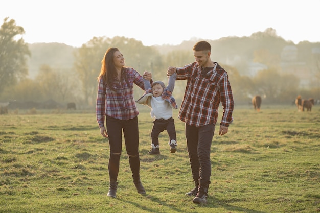 Cute family walking in a sunset summer park