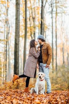 秋の公園で一緒に赤い襟の黄金のラブラドールと一緒に歩くかわいい家族