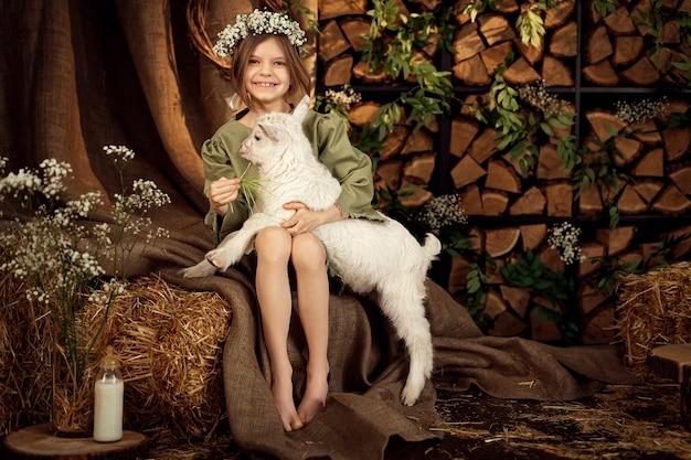 귀여운 농장 소녀가 그녀의 작은 흰 염소를 안아주고 먹이를줍니다.