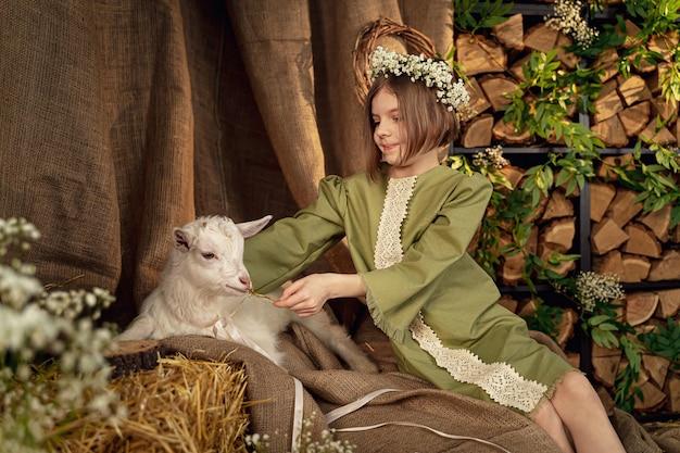 Cute farm girl hugs and feeds her little white goat