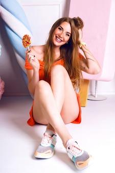 예쁜 금발의 여자, 단맛 장식, 파스텔 색상, 바닥에 siting 및 롤리팝 들고, 트렌디 한 드레스와 운동화를 입고 웃고 재미의 귀여운 패션 초상화.