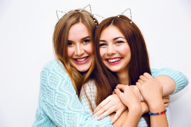 Ritratto di moda carino di belle sorelle donne che si divertono insieme abbracci e impazzire, orecchie di gatto divertenti, maglioni invernali alla menta, muro bianco, migliori amiche, gioia, tendenza, relazioni, trucco felice e naturale.