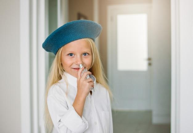 かわいいファッションのトレンディな金髪の少女は、白いシャツと青いベレー帽を着て、自宅でママのパフュームを着ています。娘はママを真似る