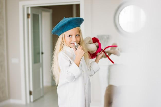 かわいいファッションのトレンディな金髪の少女は、自宅でママの香水と白いシャツと青いベレー帽に身を包んだ。娘はママを真似る