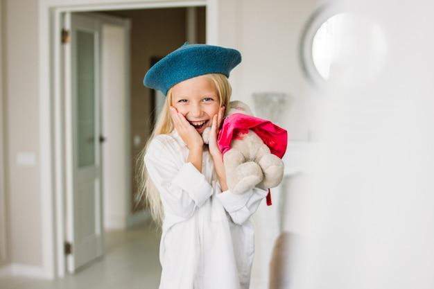 かわいいファッショントレンディな金髪の少女は白いシャツと青いベレー帽を手におもちゃで服を着た。娘はママを真似る
