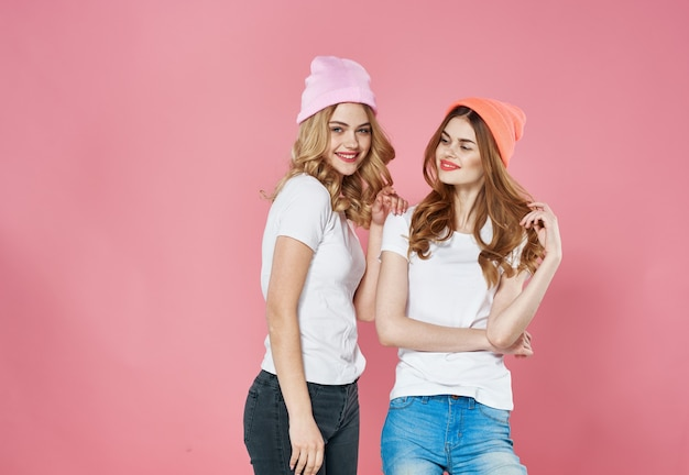 Cute fashionable girlfriends wearing lifestyle hats glamor pink.