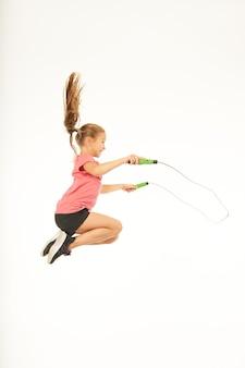 Милый ребенок женского пола в спортивной одежде смотрит в сторону и улыбается, прыгая через скакалку в воздухе. изолированные на белом фоне