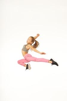 体操のトリックを作って、スタジオでジャンプしながら微笑んでいるかわいい女性の子供。白い背景で隔離