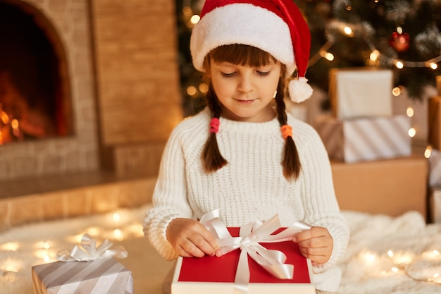 Cute female child opening present box from santa claus, wearing white sweater and santa claus hat, posing in festive room with fireplace and xmas tree.