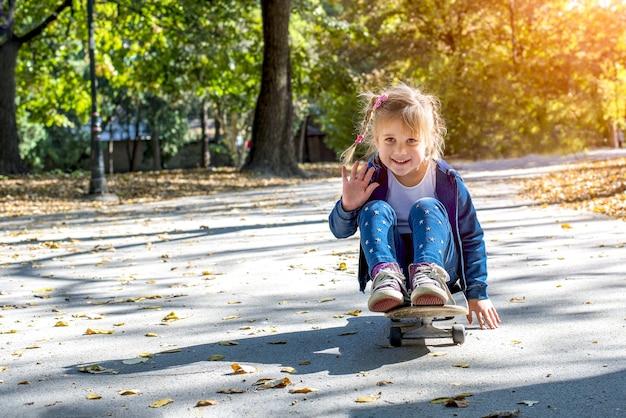 スケートボードに座って、晴れた日に公園で遊ぶかわいい女性の子供