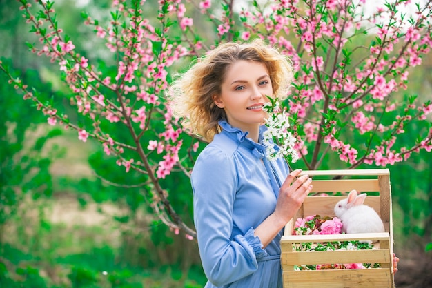 Cute female farmer working on spring field. spring woman on background with flowers on a spring day.