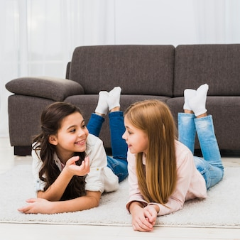 Cute female friends lying on carpet talking to each other