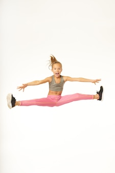 ジャンプと体操をしながら手を横に広げて叫ぶかわいい女の女の子。白い背景で隔離