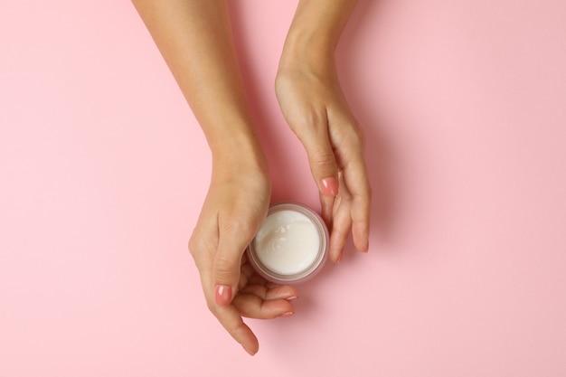 かわいい女性の手は化粧クリームの瓶を保持します