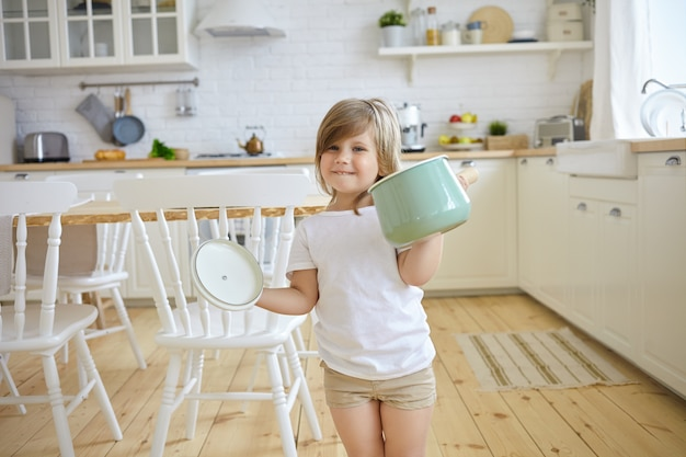 Cute female kid in casual clothes holding casserole and holder, having excited look, going to cook soup, modern kitchen