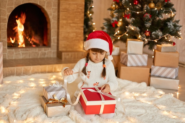 Cute female kid with pigtails sitting on floor and pulling ribbon from her present box, opening her gift, wearing pullover and santa hat, posing with fireplace and christmas tree