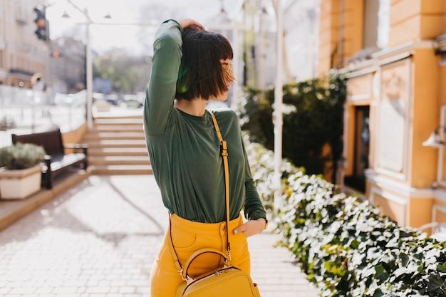 かわいい女性モデルは、散歩中にリラックスできる流行のハンドバッグを身に着けています。通りを見回している魅惑的な短い髪のブルネットの女性の屋外ショット。