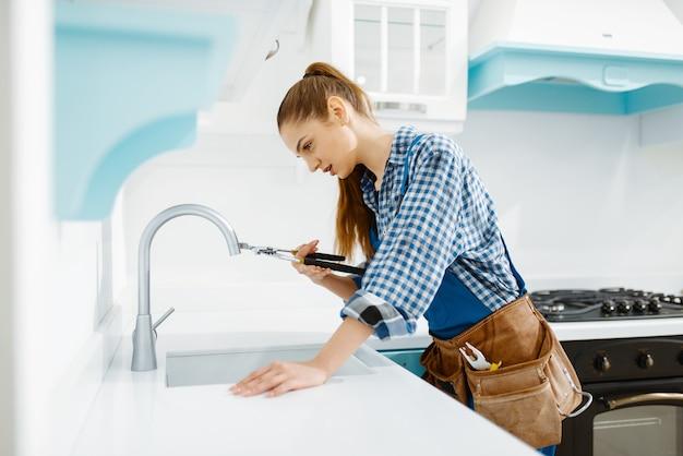 Милая женщина-сантехник в униформе фиксирует кран на кухне. разнорабочая с сумкой для инструментов ремонт раковины, сервис сантехники на дому
