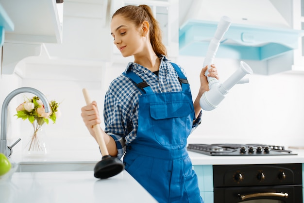 Cute female plumber in uniform holds plunger and pipe, clog in the kitchen. handywoman repair sink, sanitary equipment service at home