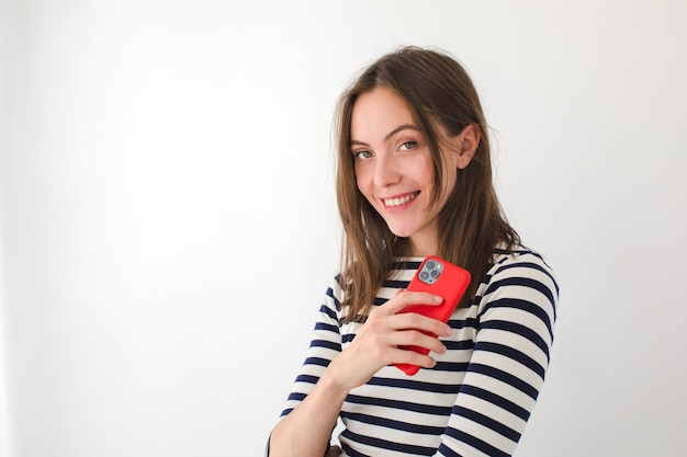 Cute female reading messages on cellphone and looking at camera while standing on a white background