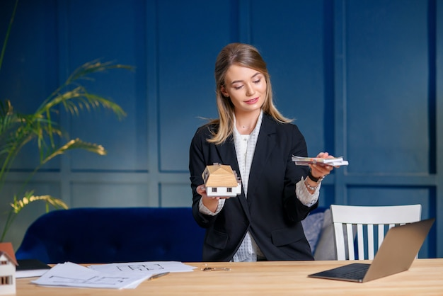 Cute female realtor with money and 3d model of house in hands