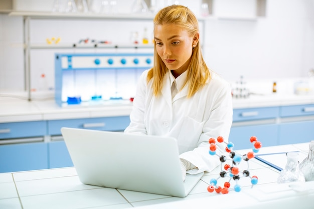 Cute female researcher in white lab coat using laptop while working in the laboratory