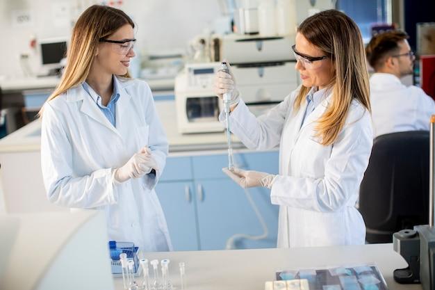Симпатичные женщины-исследователи в белом лабораторном халате работают в лаборатории