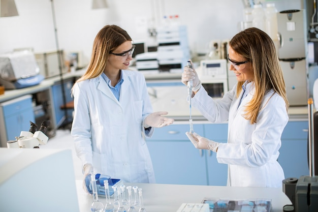 Cute female researchers in white lab coat working in the laboratory
