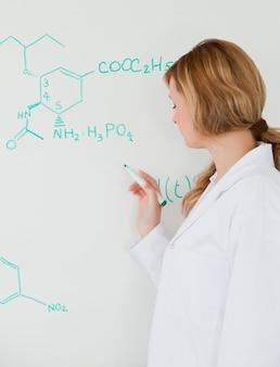 Cute female scientist writing a formula on a white board