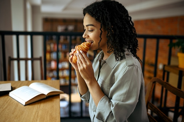 Cute female student eats croissants in cafe