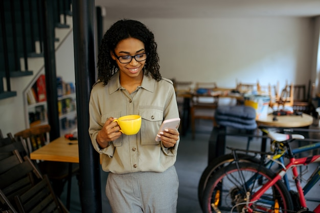 Cute female student in glasses drinks coffee and using a phone in cafe