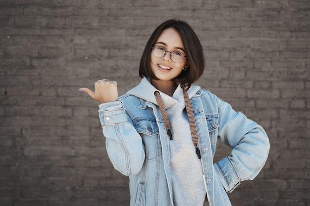 語学コースに参加する人を招待するかわいい女子学生は、若者向けの教育センターを推薦し、親指を左に向けてカメラを笑顔にし、明るい顔をして、素晴らしい場所を推薦します。