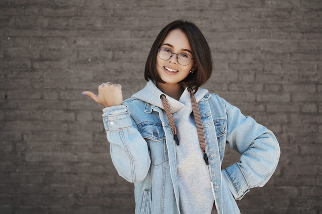 Cute female student inviting people join language courses, recommend education center for youth, pointing thumb left and smiling camera, looking upbeat, recommend awesome place.