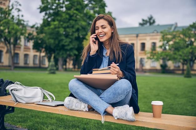 전화로 얘기하고 웃으면 서 책과 커피와 함께 벤치에 앉아 귀여운 여자 학생