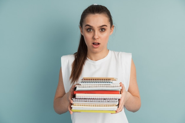 手にノートや本の山を持つかわいい女子学生