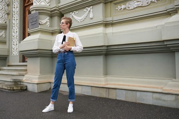 Симпатичная студентка с книгой в руках в очках ретро-здания учебного заведения