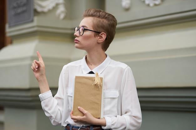 手眼鏡レトロな建物の教育機関で本を持つかわいい女子学生