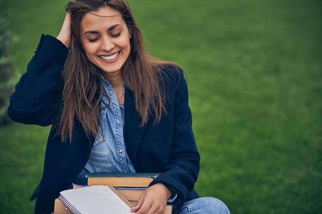 앉아서 무릎에 공부 자료를 들고있는 동안 행복하게 보이는 캐주얼 옷에 긴 머리를 가진 귀여운 여학생