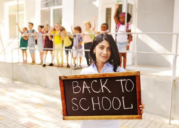 Cute female teacher with a placard saying