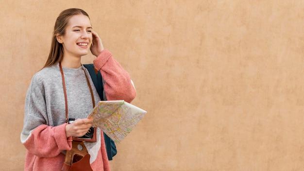 Cute female tourist holding map copy space